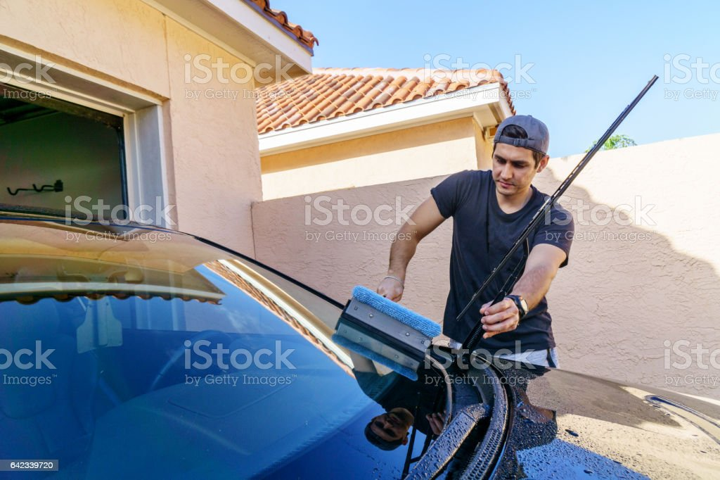 Young man washing his car stock photo
