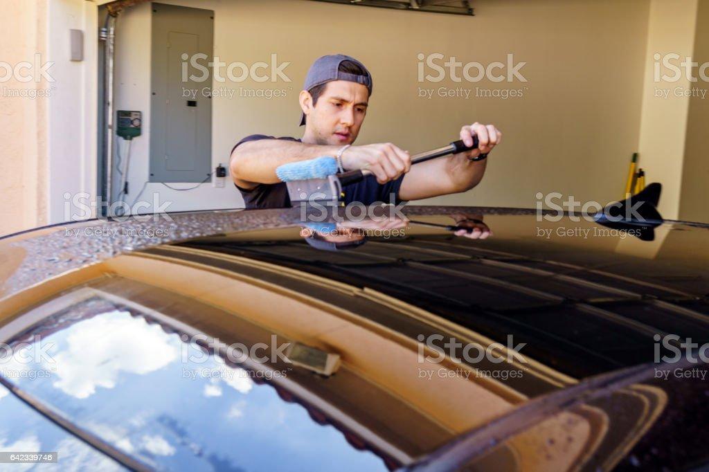 Young man washing his car stock photo