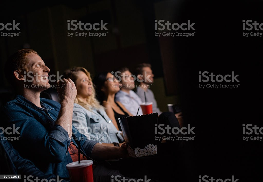 Young man watching movie with friends in cinema stock photo