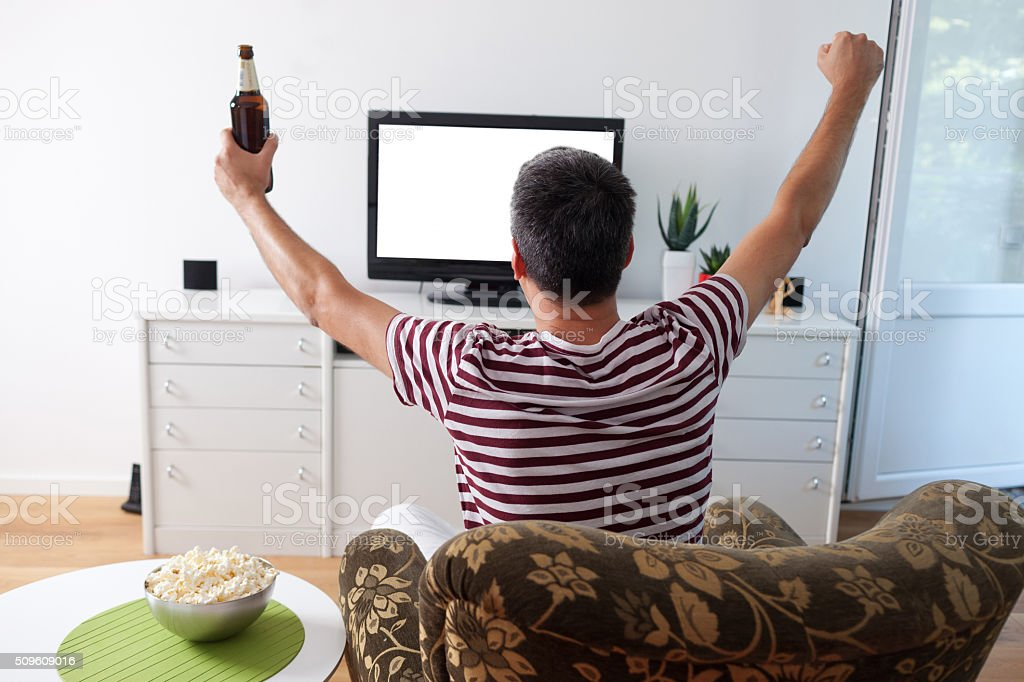 Young man watching sports stock photo