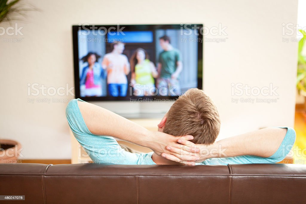 Young Man Watching Streaming Movie on TV Television stock photo