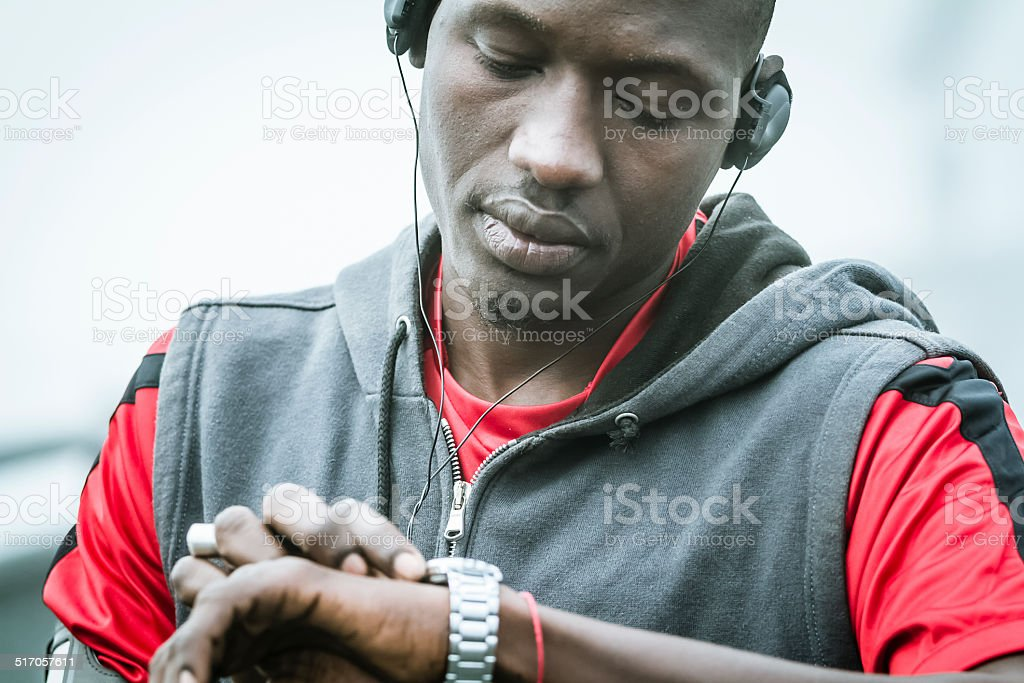 Young man watching the clock during running session stock photo