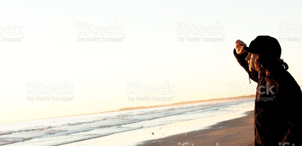 Young man watching the sunrise at waters edge royalty-free stock photo