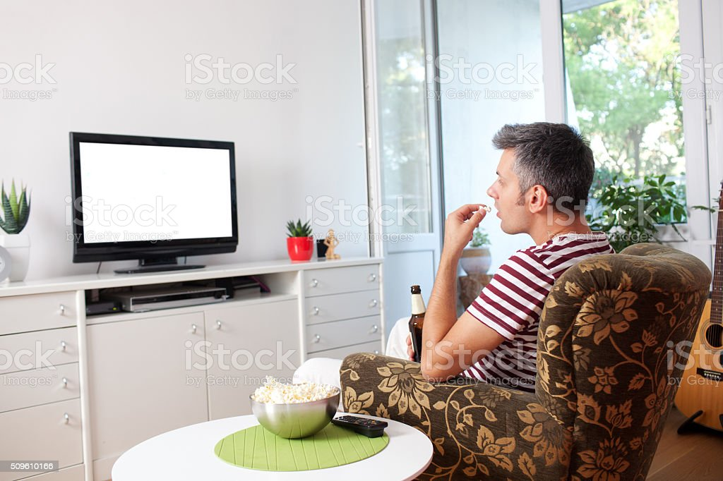 Young man watching TV stock photo