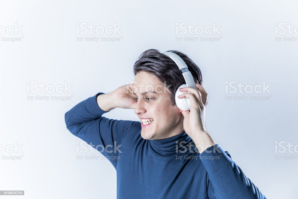 young man wearing a wireless headphone and listening to the music stock photo