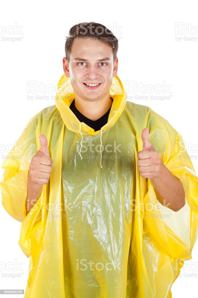 Young man wearing a yellow raincoat, showing thumbs up stock photo
