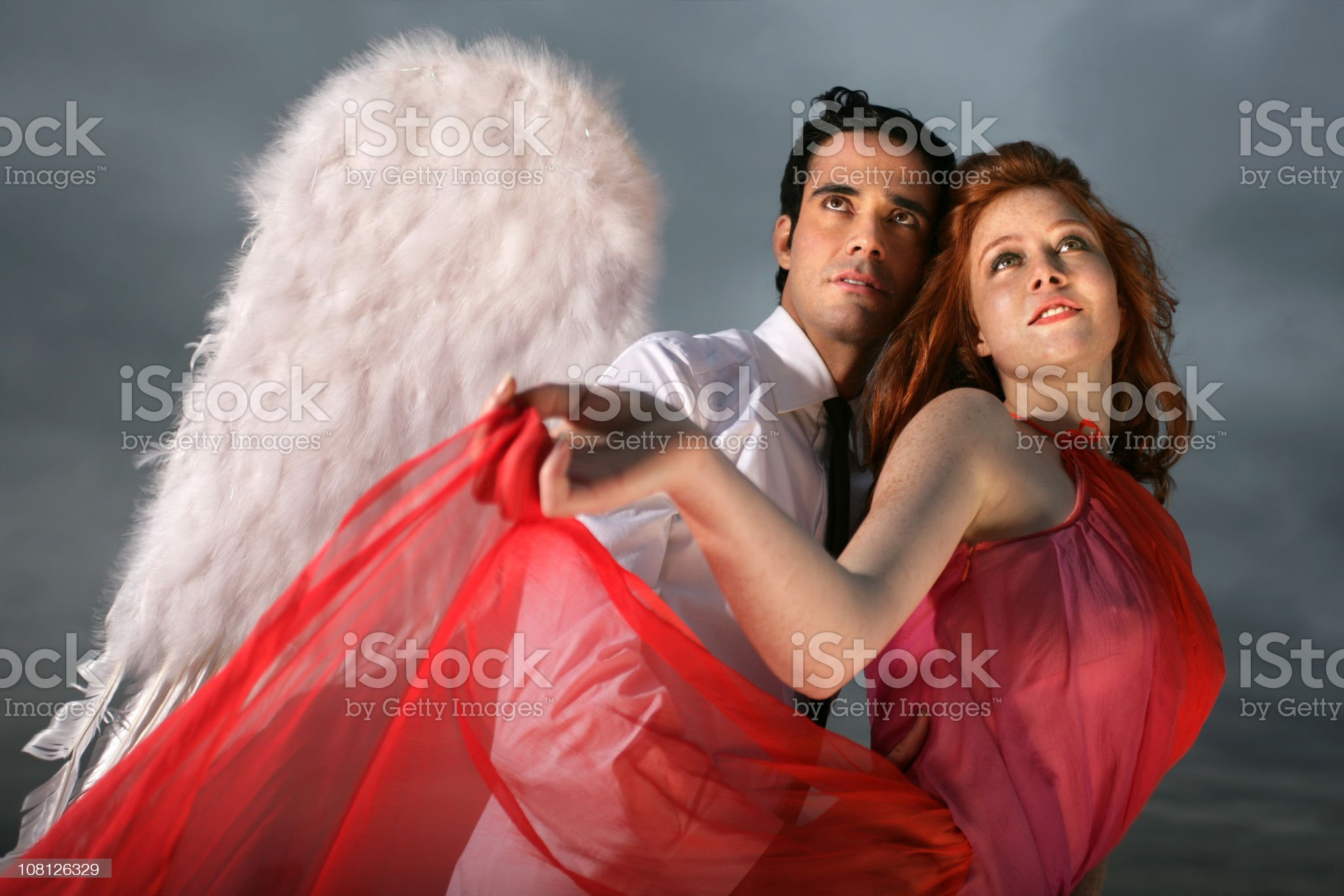 Young Man Wearing Angel Wings and Holding Woman royalty-free stock photo