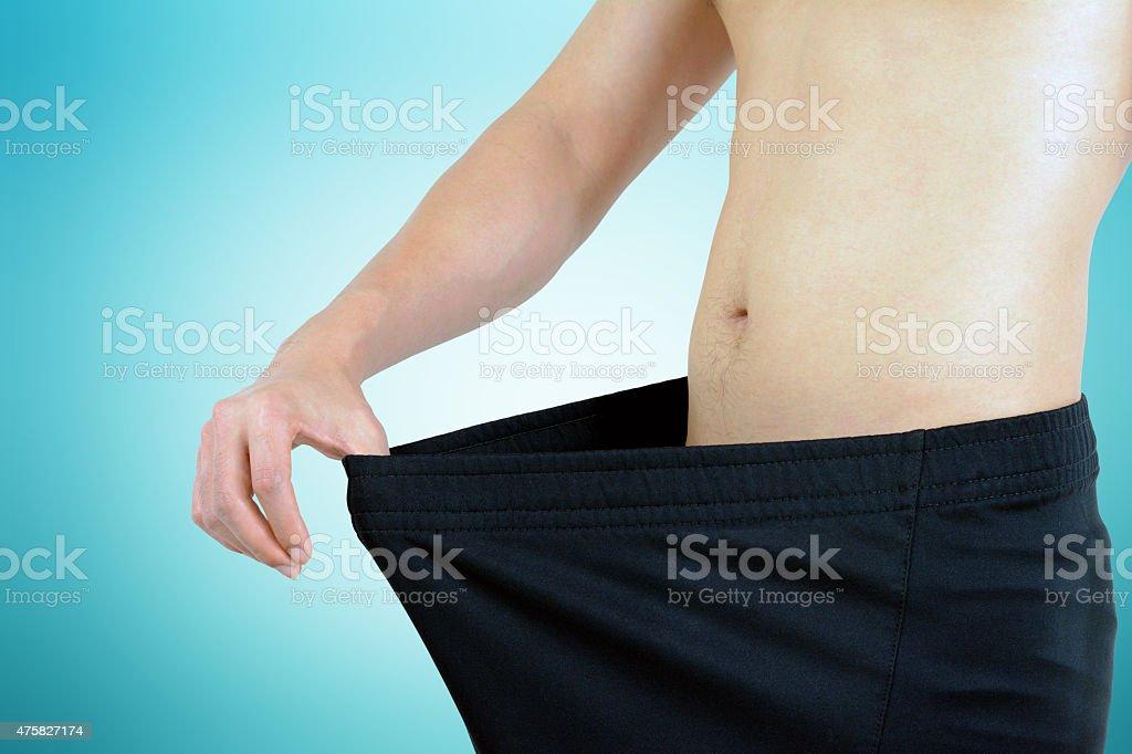 Young man wearing big loose shorts - weight loss concept stock photo