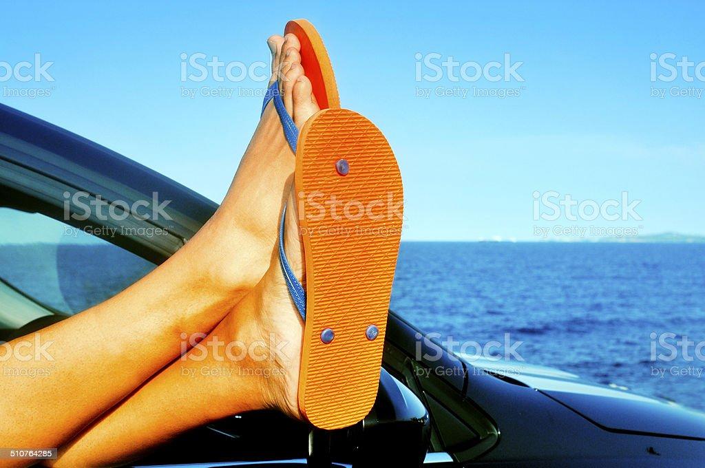 young man wearing flip-flops relaxing in a car stock photo