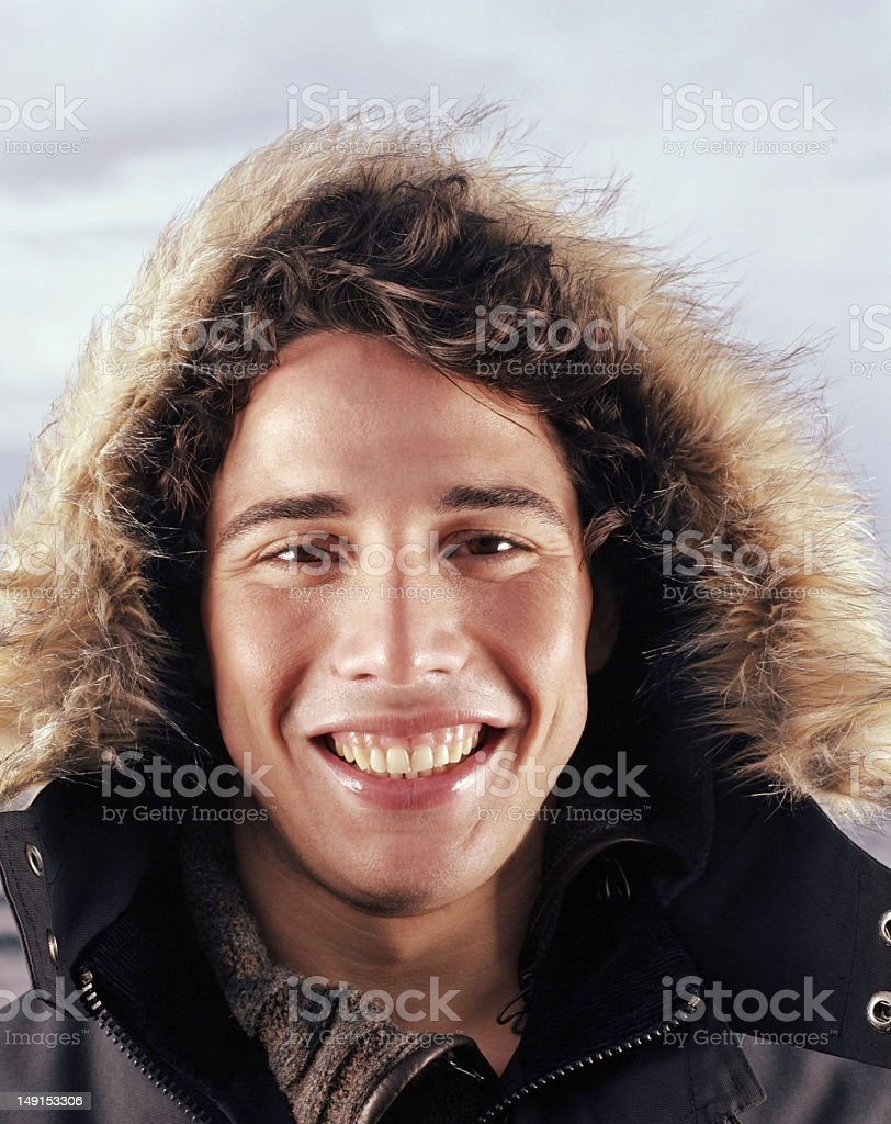 Young man wearing furry hood, smiling, portrait royalty-free stock photo