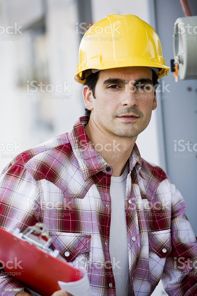 Young man wearing hardhat holding clipboard, construction worker royalty-free stock photo