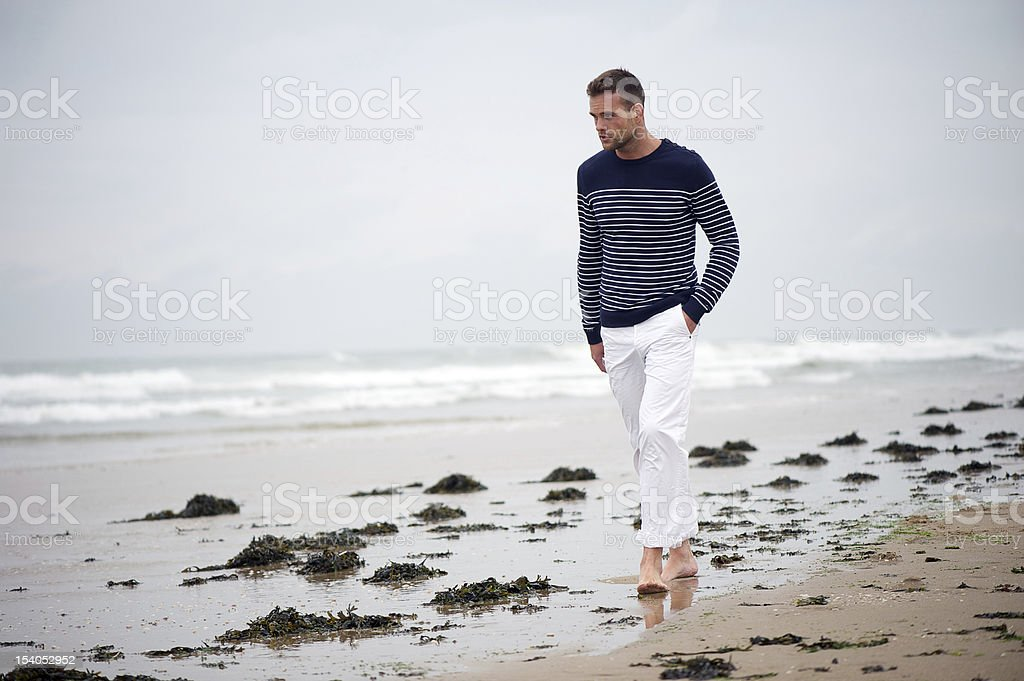 Young Man Wearing Striped Sweater Walking on the Beach stock photo