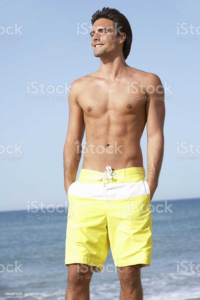 Young Man Wearing Swimming Costume Standing On Beach stock photo