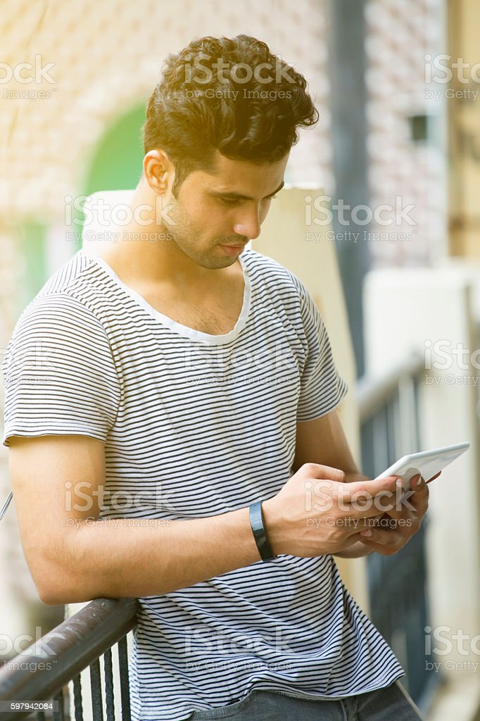 Young man wearing tracker in wrist and using digital tablet stock photo