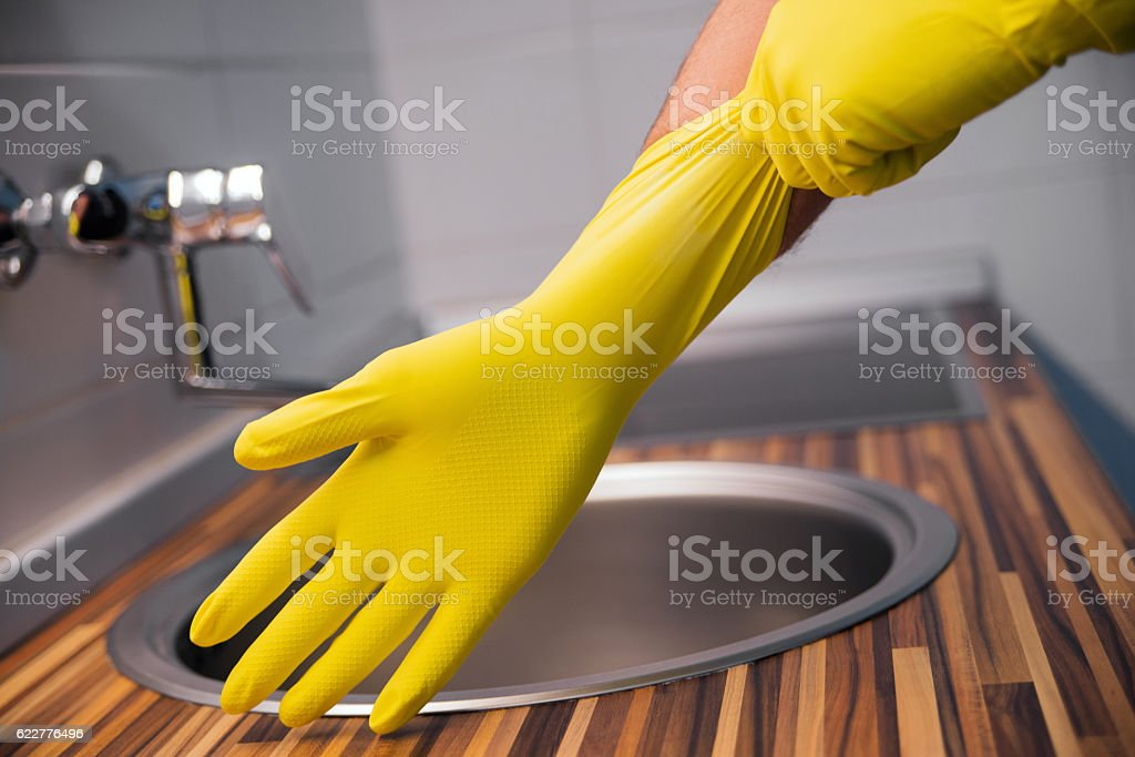 Young man wearing yellow rubber gloves. Ready to cleaning stock photo