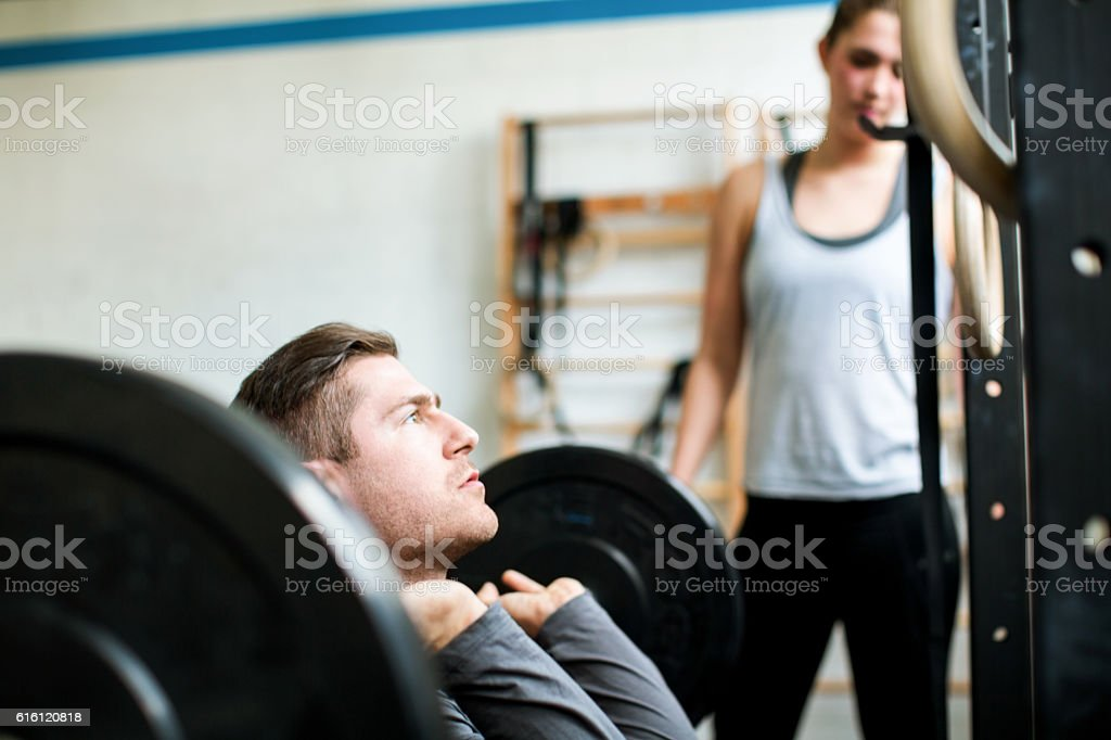 Young man weight lifting with female trainer in gym stock photo