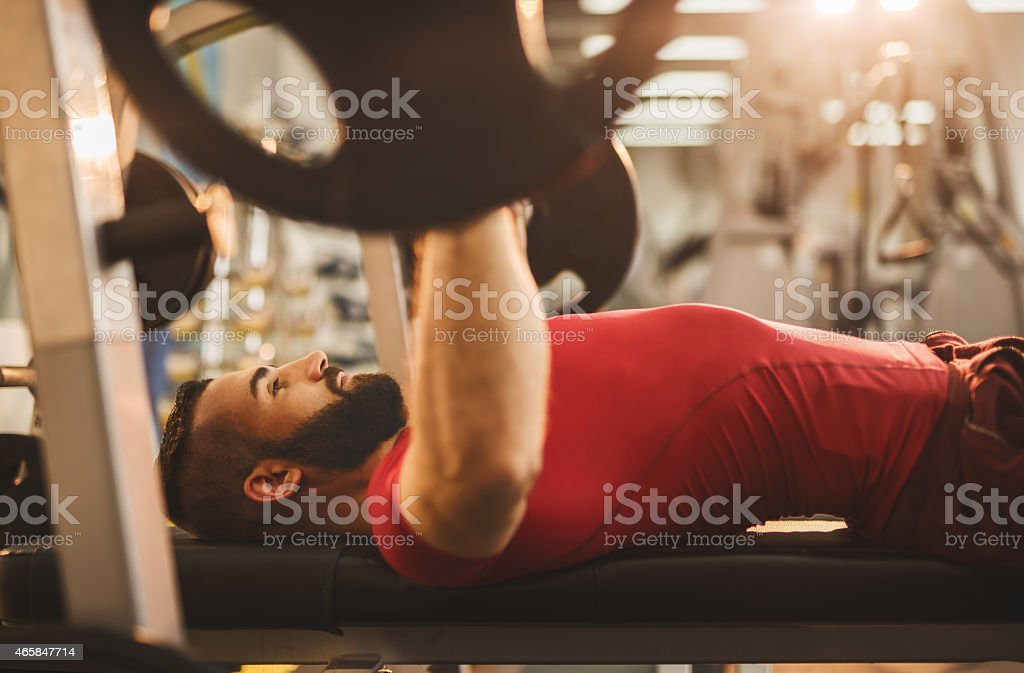 Young man weightlifting on a weight bench in gym. stock photo