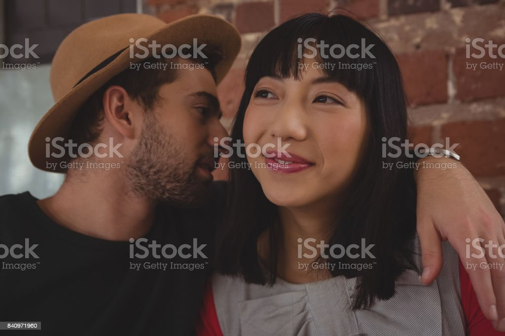 Young man wearing hat whispering in woman ear at cafe