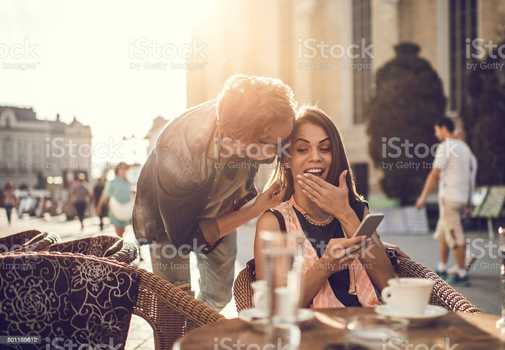 Young man whispering shocking things to his girlfriend at cafe. stock photo