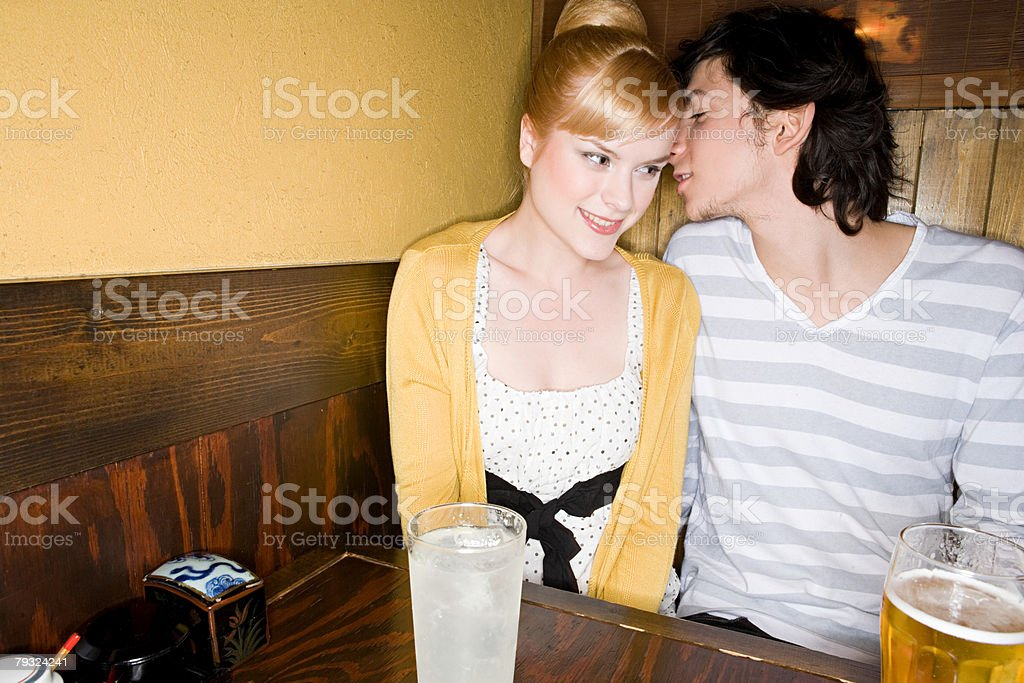A young man whispering to a woman royalty-free stock photo