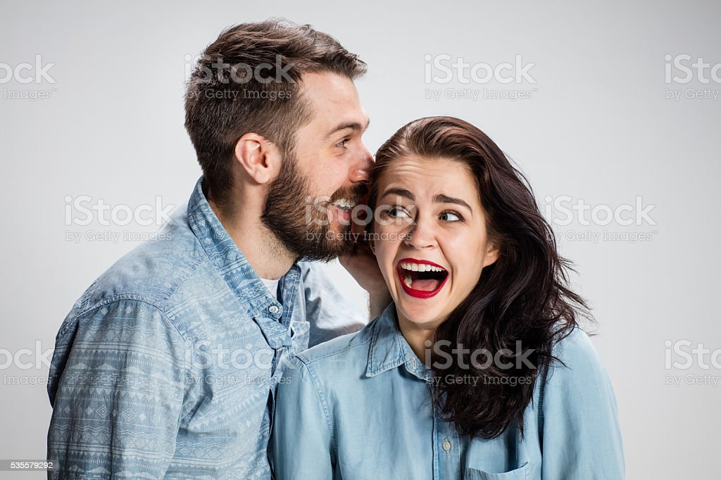 Young man whispering to woman a secret stock photo