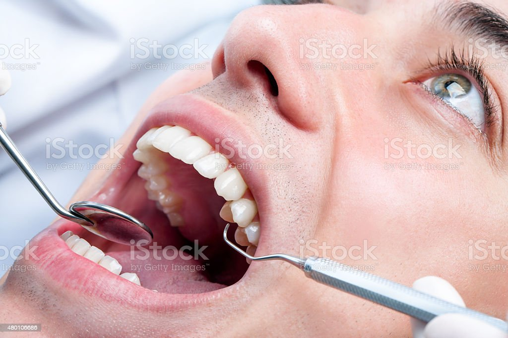 Young man whitening teeth at dentist. stock photo