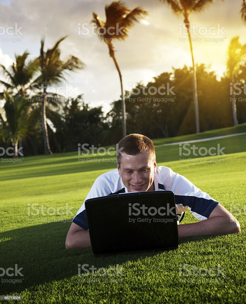 young man whith notebook on the green field royalty-free stock photo