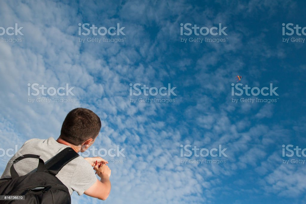 Young man with a backpack holding kite flying in a blue sky stock photo