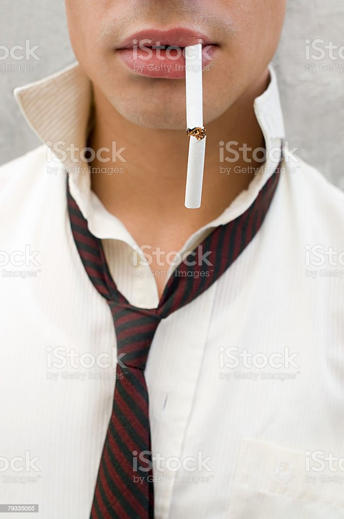 Young man with a cigarette in mouth stock photo