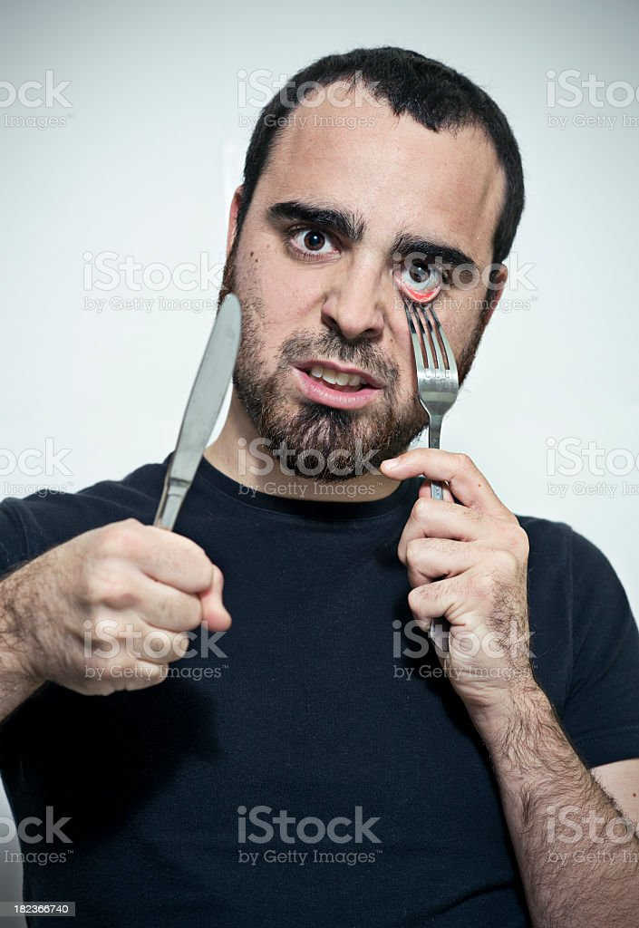 Young man with a fork in his eye stock photo