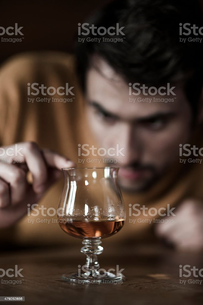 Young man with a glass of brandy stock photo