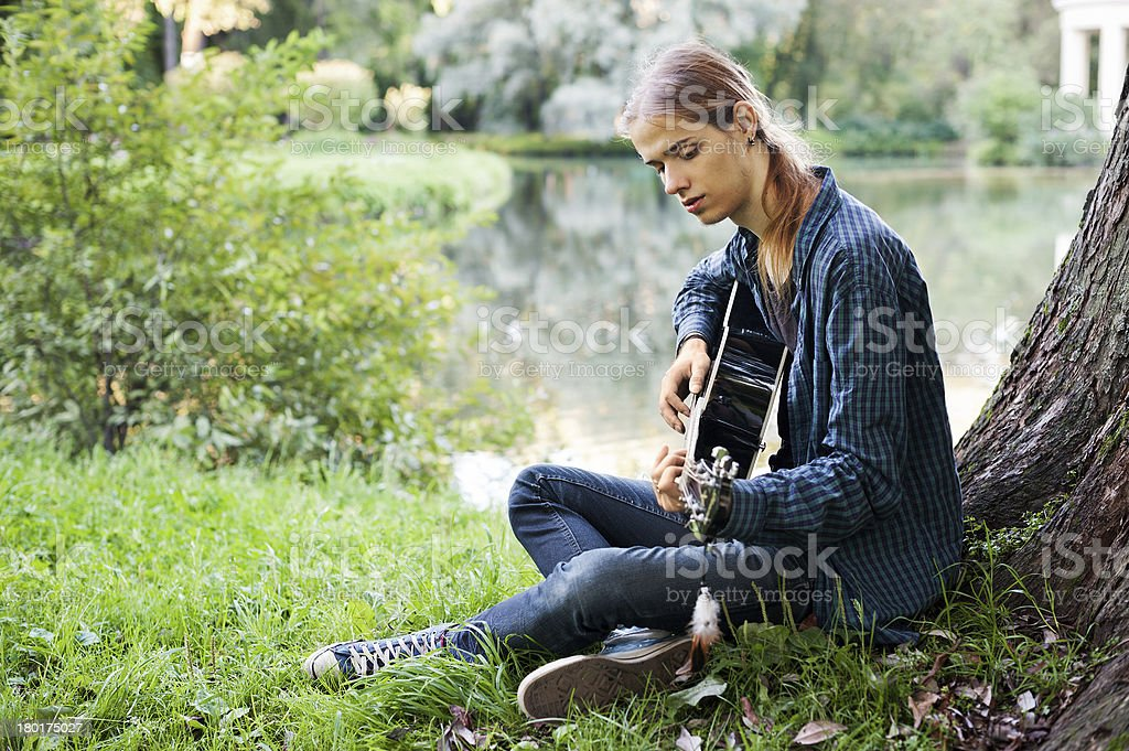 Young man with a guitar in the summer park royalty-free stock photo