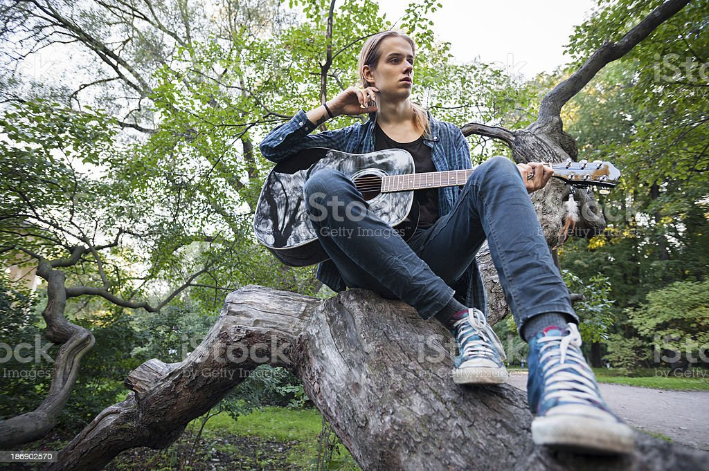 Young man with a guitar in the summer park stock photo