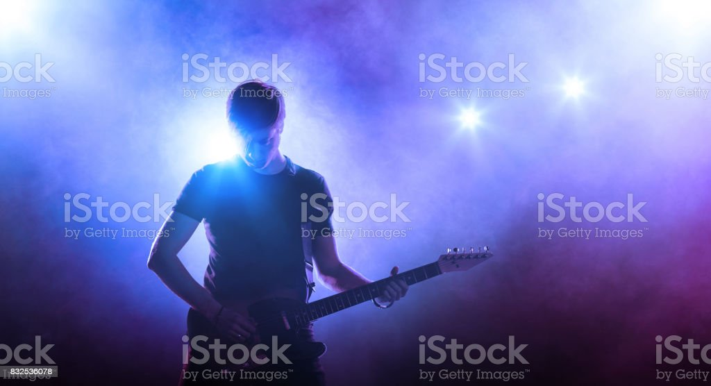 Young man with a guitar on stage stock photo