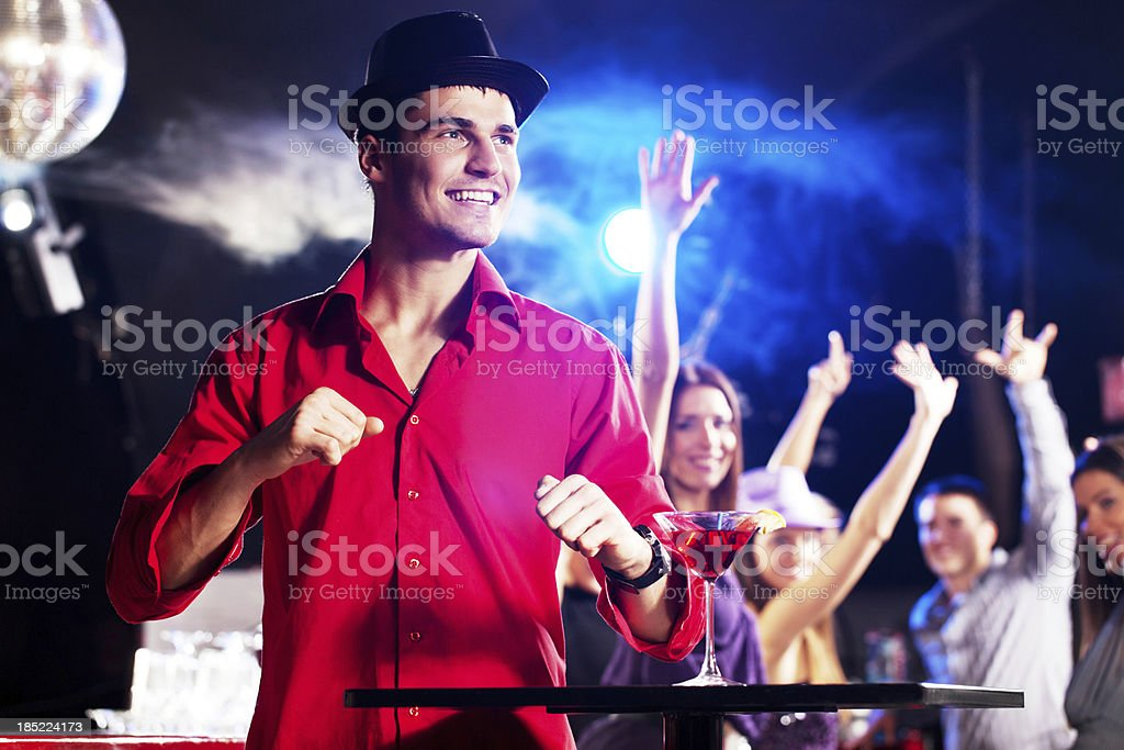 Young man with a hat is dancing in the discotheque. royalty-free stock photo