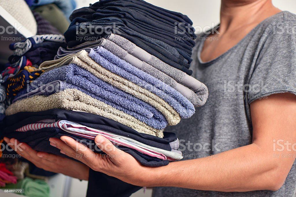 young man with a pile of folded clothes stock photo