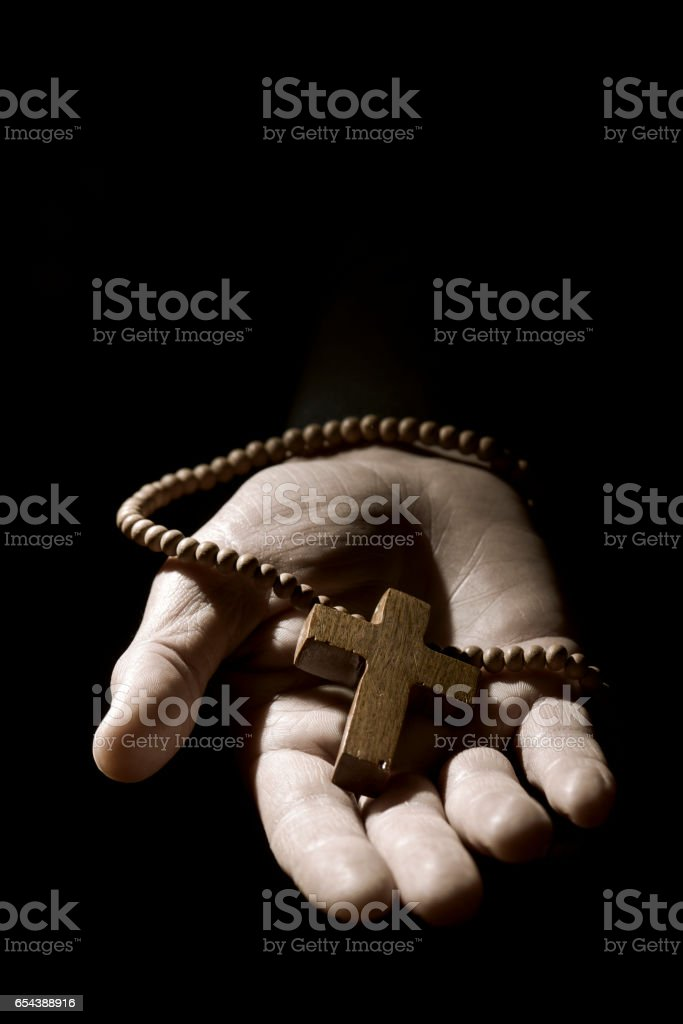 young man with a rosary in his hand stock photo