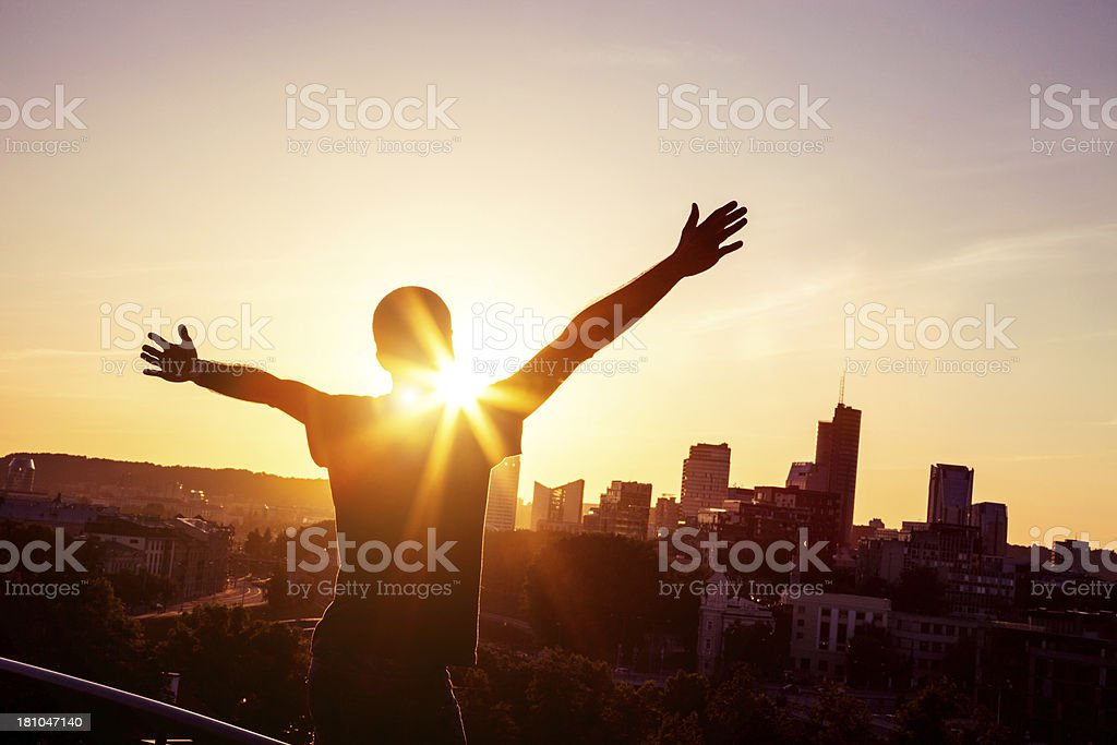 Young man with arms raised in front of the skyline stock photo