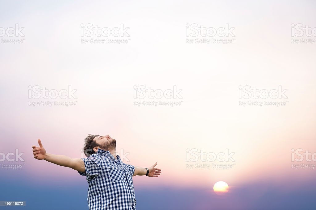 Young man with arms raised stock photo