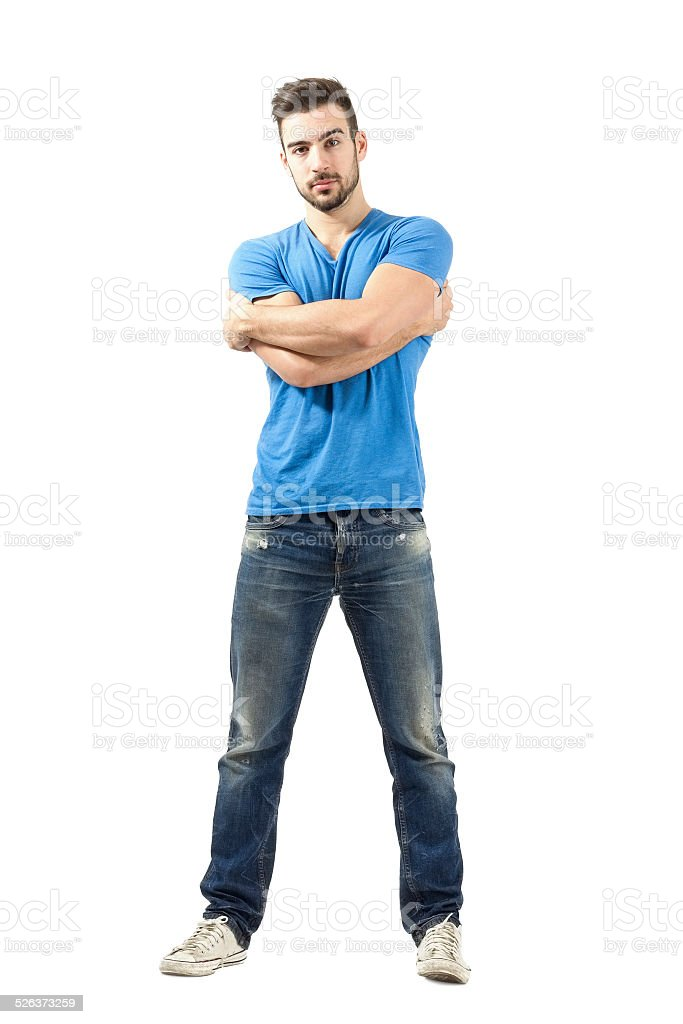 Young man with arms wrapped around himself looking at camera stock photo