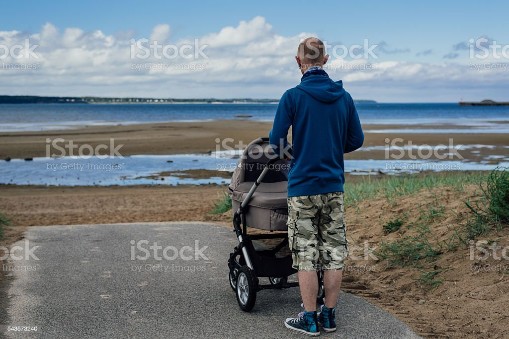 Young man with baby stroller on beach stock photo
