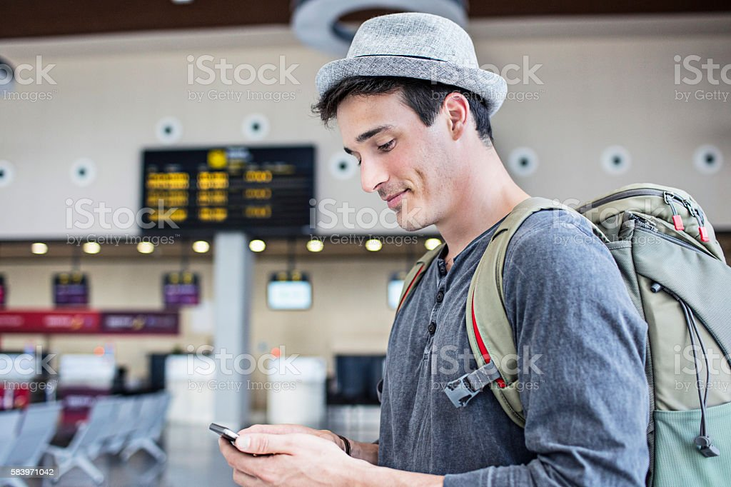Young man with backpack and cell phone in airport stock photo
