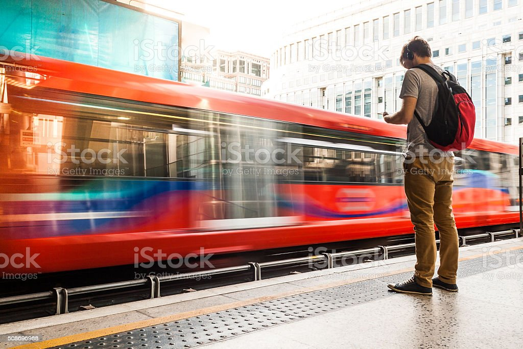 A photo of a young man wearing headphones while waiting for the...