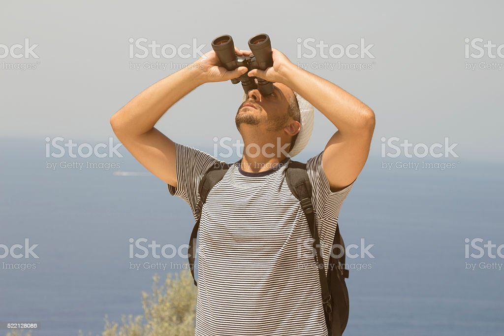 Young man with backpack looking through binoculars outdoors stock photo