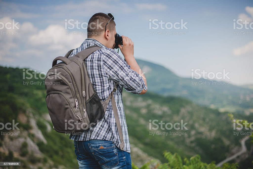 Young man with backpack taking a photo stock photo