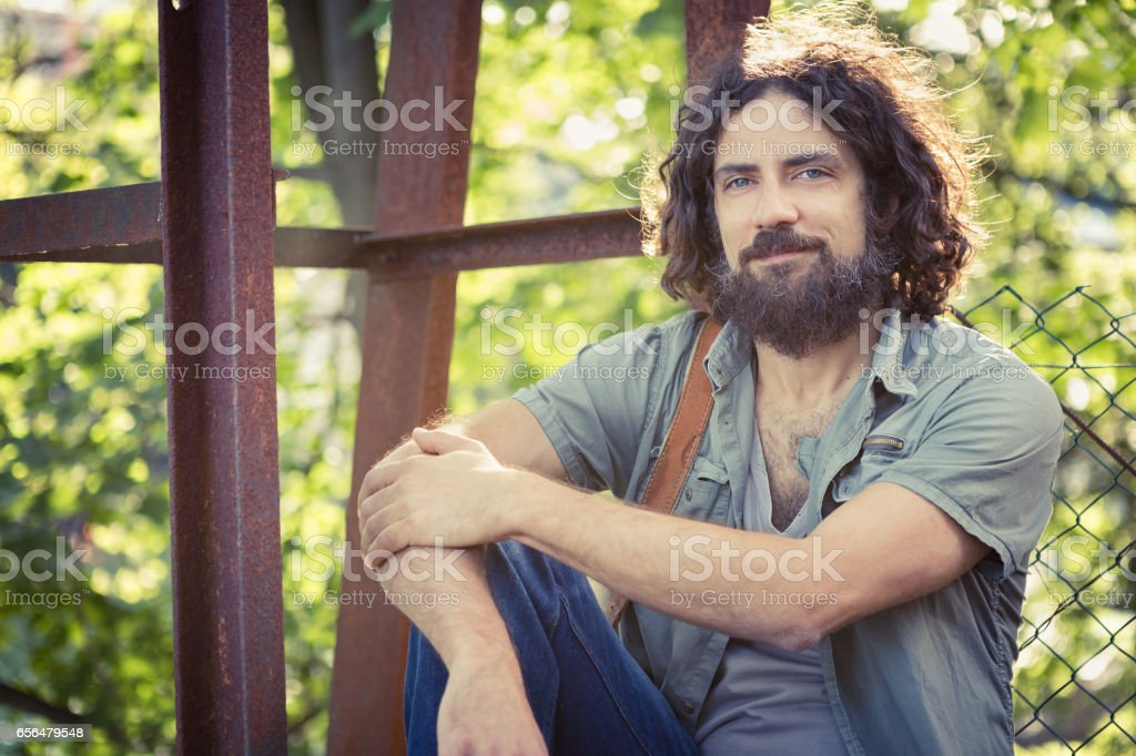 young man with beard in the park stock photo