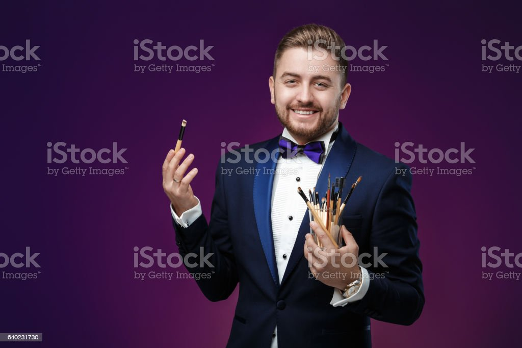 young man with beard in tuxedo holds makeup brush and stock photo