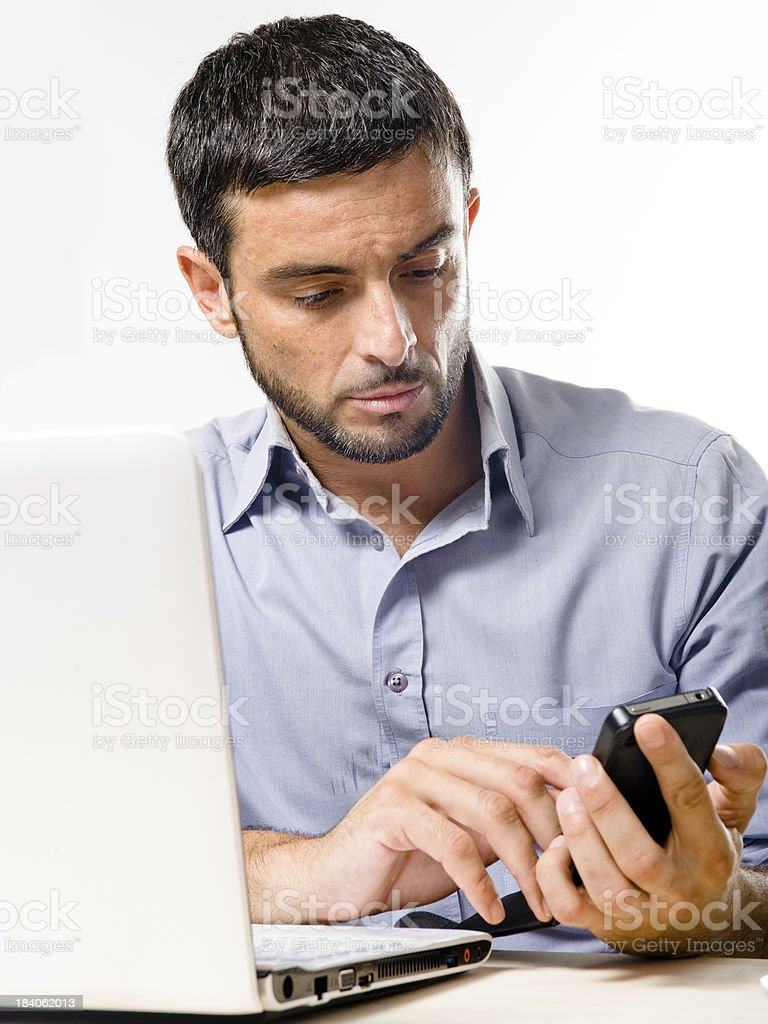 Young Man with Beard working on Laptop and Cellphone royalty-free stock photo