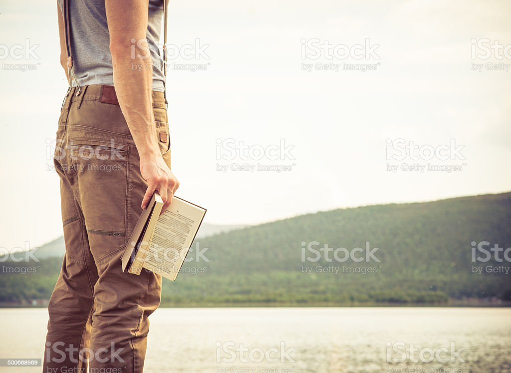 Young Man with book outdoor Summer vacations Lifestyle stock photo