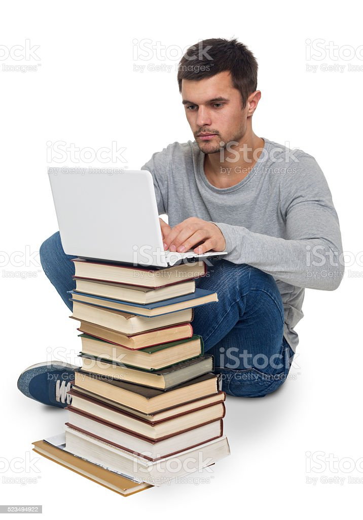 Young man with books and computer stock photo